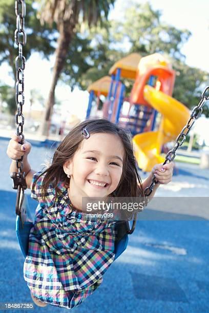 Mignonne petite fille se balancer sur le parc