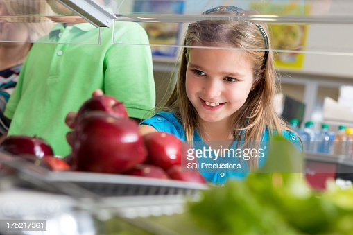 Cute little girl taking apple in school lunch line