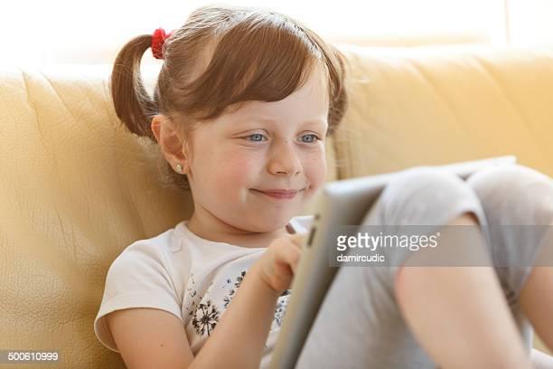 Niedliche kleine Mädchen mit einem digitalen tablet