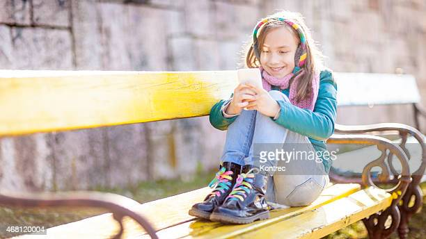 Cute little girl using her mobile phone outdoors