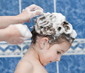 Cute little girl washing hair in bath.