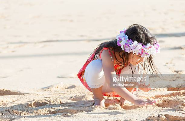 Cute little girl wearing a lei plays on Hawaiian beach