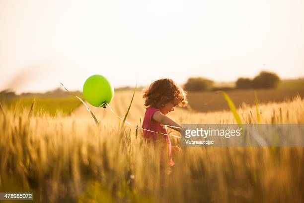 Cute little girl with balloons at field