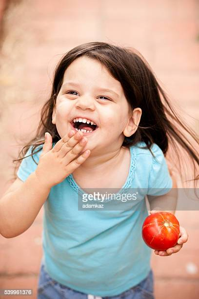 Cute Little Girl with freshly picked tomato from garden