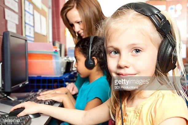Bambina carina con cuffie lavorando sul Computer a scuola