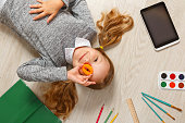 Cute little girl with O letter lying on the floor. The child is surrounded by a book, tablet, paints, brushes, pencils.