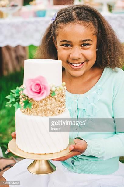 Linda niña con bastante una porción de torta en una fiesta