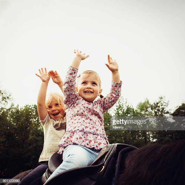 Cute little girls smiling while learning horseback riding