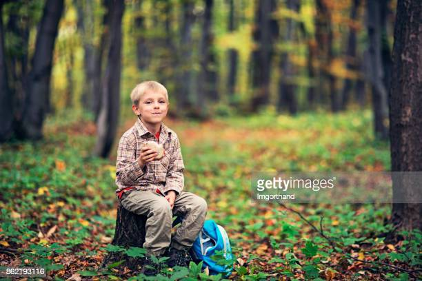 Cute little hiker resting in forest