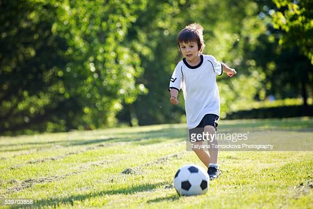 Cute little kid, playing football, summertime. Children playing soccer outdoor