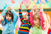 Cheerful group of small kids with raised arms enjoying while dancing.
