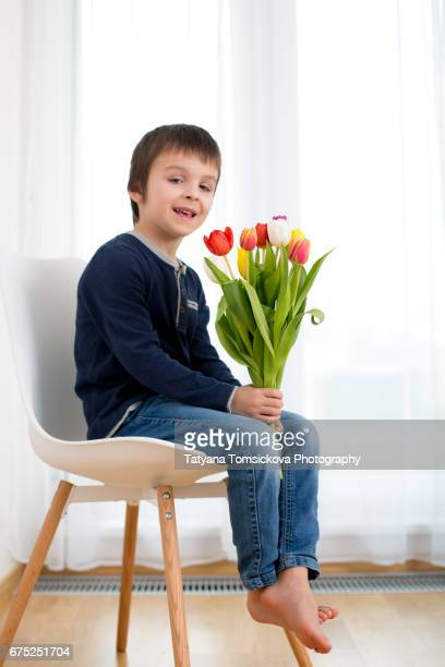 Cute little preschool boy, holding big bouquet of tulips, flowers for mom for mother's day