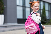 cute little redhead schoolgirl in eyeglasses holding backpack and smiling at camera