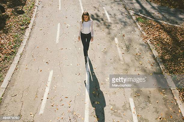 Cute lonely girl walking down the street in autumn
