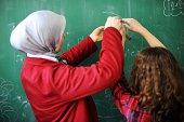 Arabic Muslim teacher showing school girls on the classroom board
