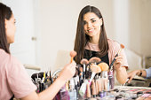 Portrait of a gorgeous Hispanic make-up artist choosing a brush while working in her beauty studio