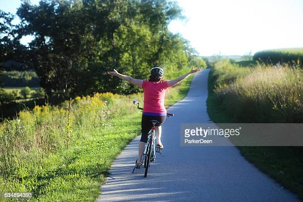 Cute Mature Woman Riding Her Bike Down Sunlit Trail