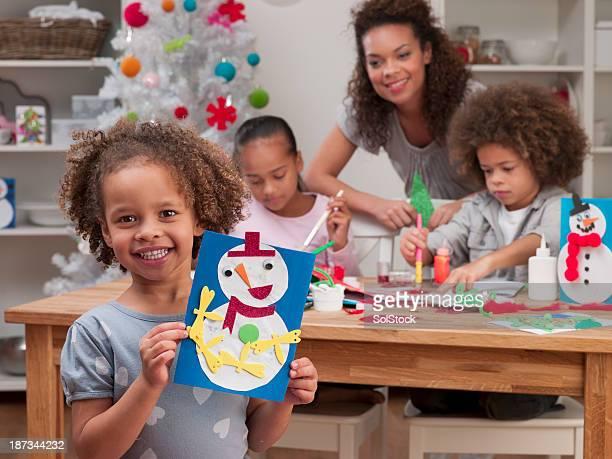 かわいい異人種手作りのクリスマスカードを持つ少女
