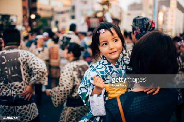 Cute mixed race little girl in yukata with her mother at traditional festival in Tokyo