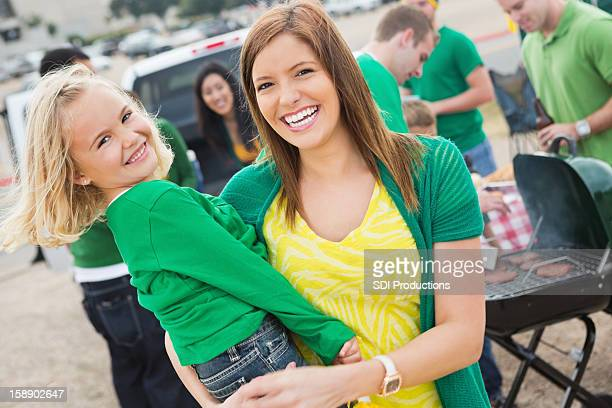 Cute mom and daughter at college football stadium tailgate cookout