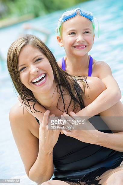 Cute mom and elementary age daughter swimming in pool together