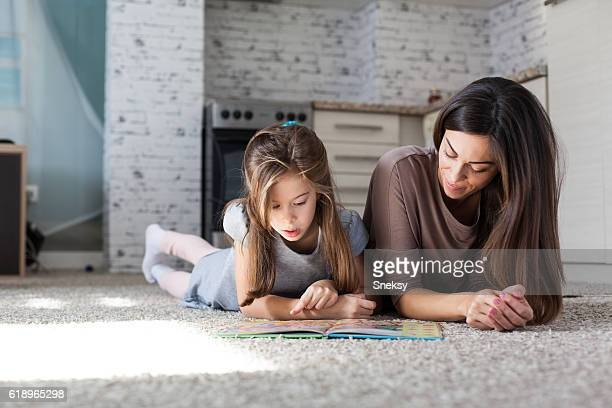 Cute mother and daughter reading book