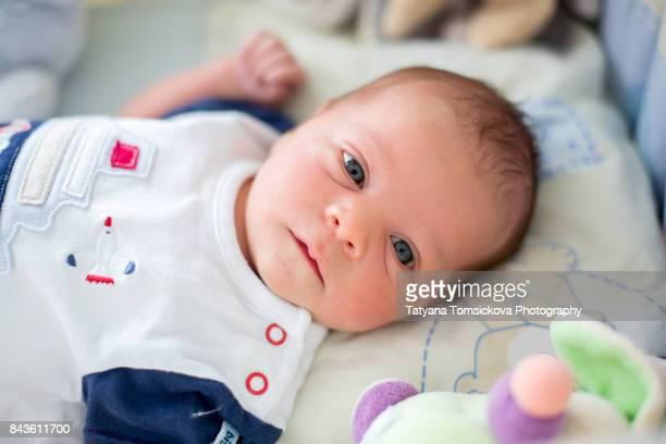 Cute newborn baby boy, playing in crib, toys around him