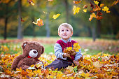 Cute preschool child, boy, playing with leaves in the park, autumn on sunset, back light. Selective focus