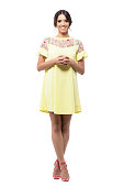 Cute pretty smiling woman in yellow dress standing with clasped hands looking at camera. Full body length portrait isolated on white background.