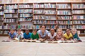 Cute pupils and teacher lying on floor in library at the elementary school