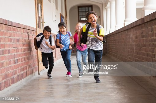 Cute pupils running down the hall : Stock Photo