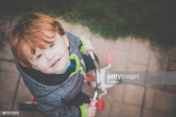 Cute Redhead Baby Boy Smiling on Tricycle