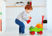 cute redhead toddler baby collecting different balls into toy pushcart