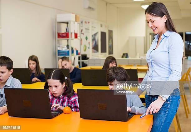 Scuola bambini carino utilizzando un computer portatile a scuola
