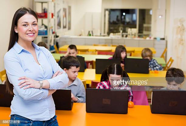 Cute school children using laptop at school