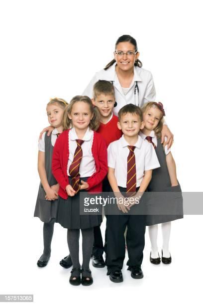 Cute School Kids With A Doctor, Studio Portrait