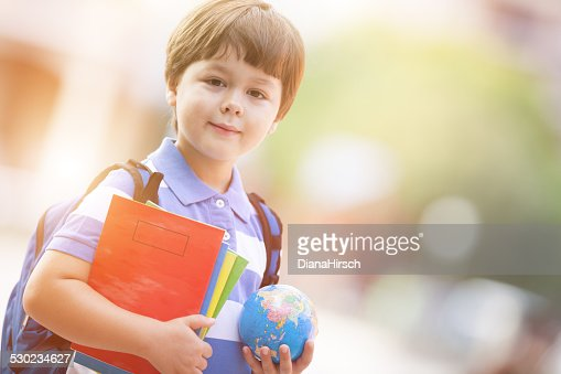 cute schoolboy in the schoolyard with school supplies
