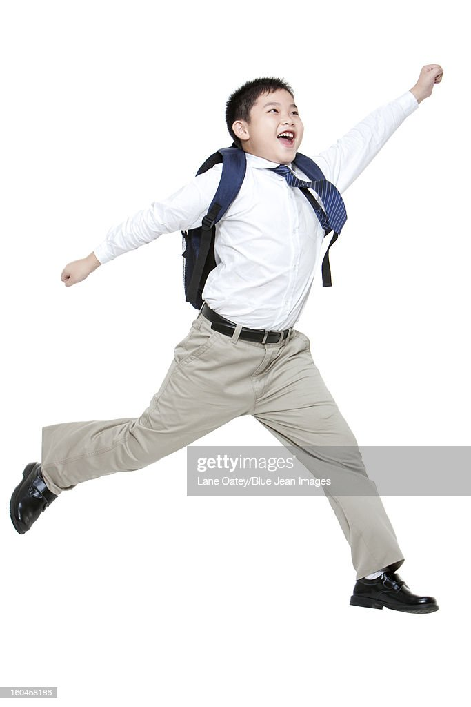 Cute schoolboy jumping excitedly with schoolbag on the back