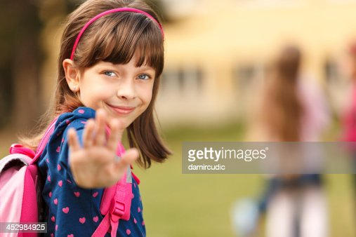 Cute schoolgirl in front of the school
