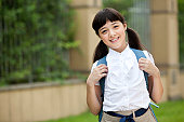Cute schoolgirl in uniform carrying schoolbag on the back at school yard