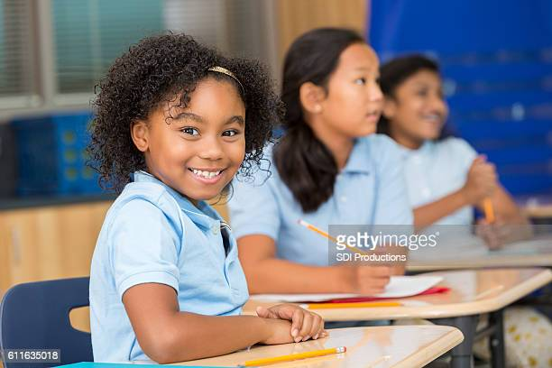 Cute schoolgirl smiles at the camera in classroom