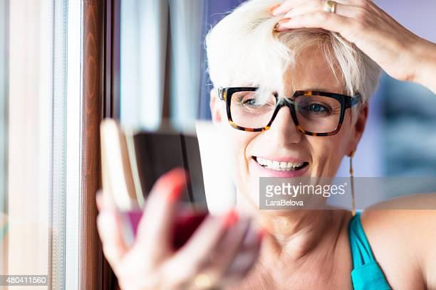 Süße senior Frau auf der Suche in Spiegel der powder