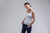Cute sexy woman with lovely dimples and a sweet playful smile posing with hands in pockets in a graceful pose isolated on grey with copy space