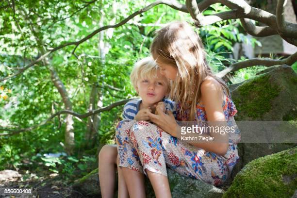 Cute siblings hugging, sitting on a rock in the garden