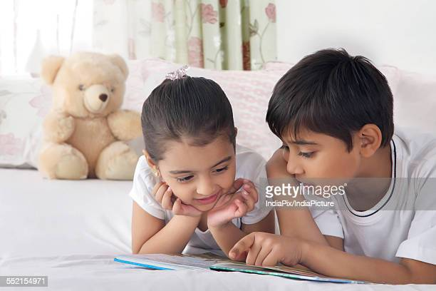 Cute siblings reading book in bed