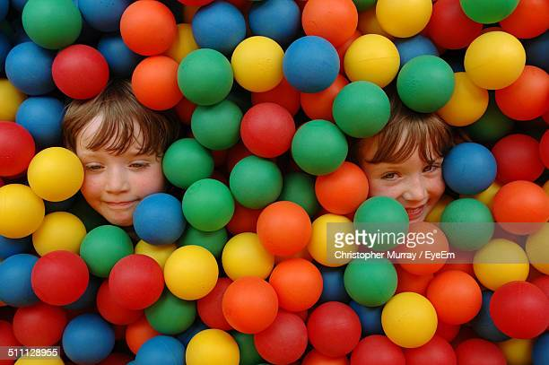 Cute sister and brother surrounded by colorful balls