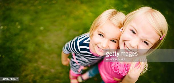 Cute sisters looking up at camera while hugging