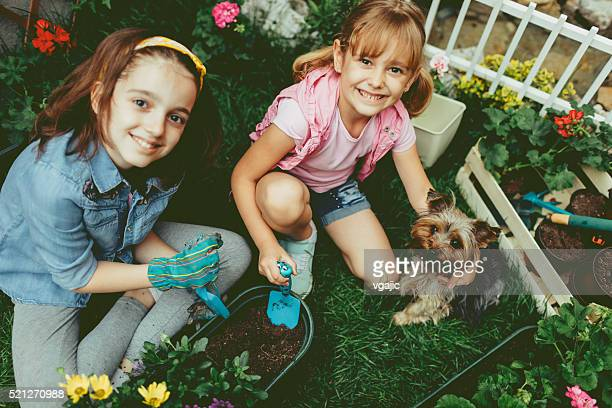 Cute Sisters Planting Flowers With Their Pet Dog