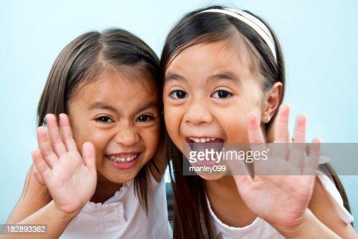 cute sisters waving hi at camera