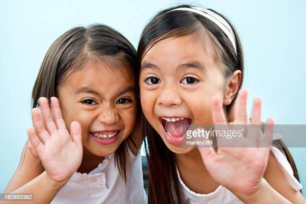 cute sisters waving hi at camera